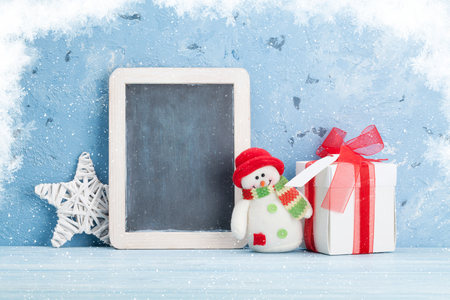 xmas background: Christmas chalkboard, snowman and gift box. View with copy space for your text