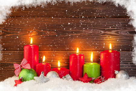 velas de navidad: Christmas background with candles in snow in front of wooden wall with copy space