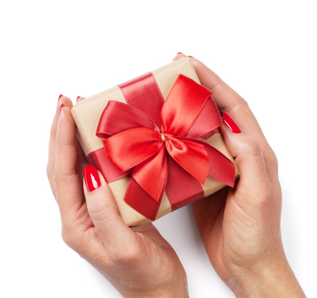 female christmas: Female hands holding christmas or valentines day gift. Isolated on white background. Top view Stock Photo