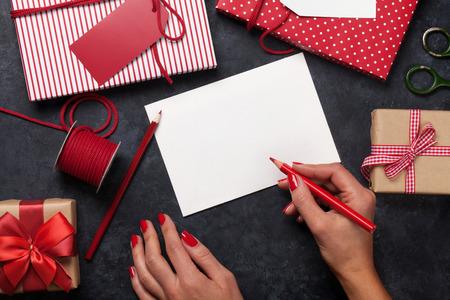 Vrouwelijke kerstmis wenskaart en geschenkverpakking boven stenen tafel. Bovenaanzicht met kopie ruimte Stockfoto
