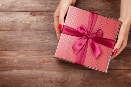 Female hands holding christmas or valentines day gift above wooden table. Top view with copy space Фото со стока - 64456868