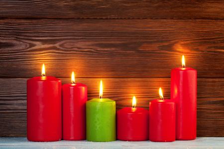velas de navidad: Velas de Navidad en frente de la pared de madera con espacio de copia