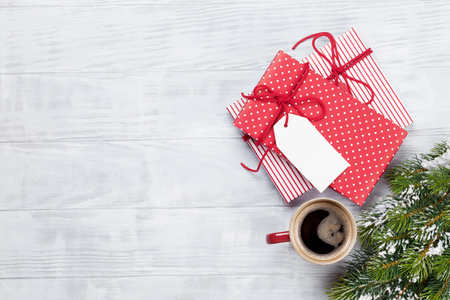 Christmas gift box, coffee cup and fir tree on wooden background. Top view with copy space