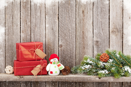 Christmas gift boxes and snowman toy in front of wooden wall. View with copy space Stock Photo