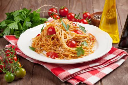 comida italiana: Spaghetti pasta with tomatoes and parsley on wooden table