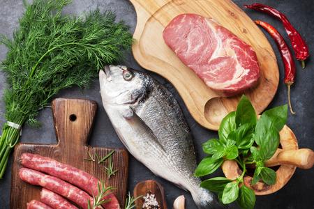 Salchichas, pescado, carne y los ingredientes para cocinar. Vista superior de una mesa de piedra Foto de archivo - 65261077