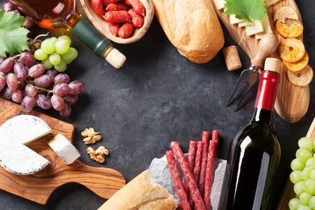 Botellas de vino tinto y blanco, uva, queso y salchichas sobre la mesa de piedra. Vista superior con espacio de copia Foto de archivo - 65261080