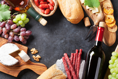 Red and white wine bottles, grape, cheese and sausages over stone table. Top view with copy space