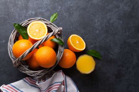 fruits juice: Fresh orange fruits and juice on stone table. Top view Stock Photo