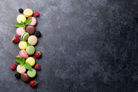 Colorful macaroons and berries on stone table. Sweet macarons with strawberry, raspberry and blackberry. Top view with copy space Stock Photo