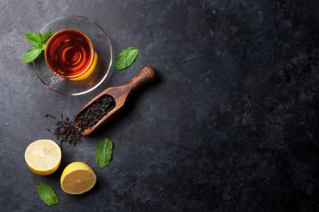 Theekopje met munt en citroen en droge thee in lepel op stenen tafel. Bovenaanzicht met kopie ruimte