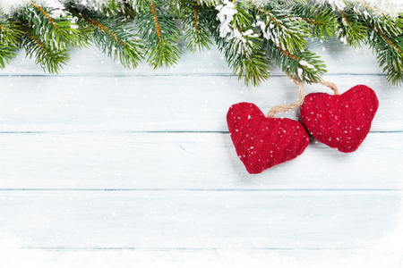 hearts background: Christmas wooden background with snow fir tree and decoration. Top view with copy space for your text