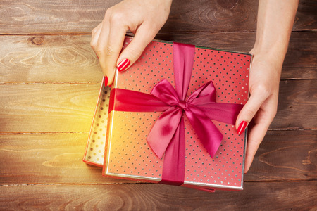 Female hands opening christmas or valentines day gift box above wooden table. Top view Stock Photo