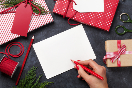 female christmas: Female writing christmas greeting card and gift wrapping above stone table. Top view with copy space