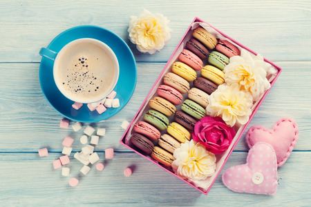 Colorful macaroons, coffee and marshmallow on wooden table. Sweet macarons in gift box and hearts. Top view. Retro toned
