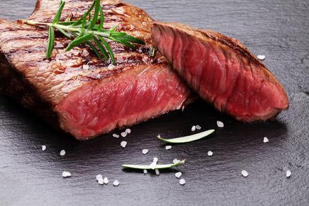 carne asada: Filete de ternera a la plancha con romero, sal y pimienta en la placa de piedra negro Foto de archivo