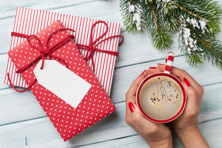 hand hold: Female hands holding coffee cup, christmas gift boxes and snow fir tree above wooden table. Top view with copy space Stock Photo