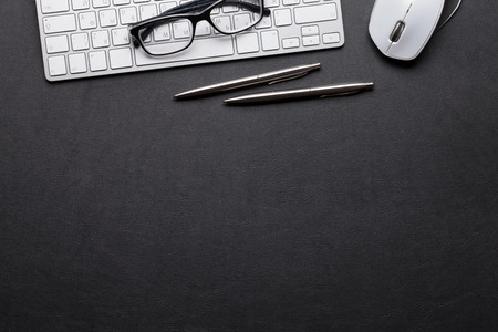 Biurowy skórzany stolik biurkowy z komputerem, okularami, ołówkiem i długopisem. Widok z góry z miejscem na kopię Zdjęcie Seryjne