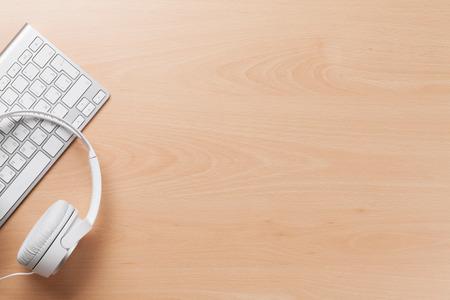 trompo de madera: Auriculares sobre el teclado de la PC en la mesa de escritorio de madera. Concepto de la música. Vista superior con espacio de copia Foto de archivo