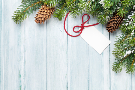 Christmas background with gift label and fir tree on wooden table. Top view with copy space. Gift wrapping Stock Photo