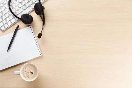 Bureau met headset, blocnote en pc. Call center support tafel. Top veiw met kopie ruimte