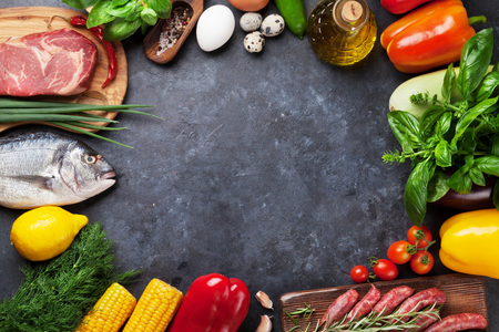 Verdure, pesce, carne e ingredienti da cucina. Pomodori, melanzane, mais, carne di manzo, uova. Vista dall'alto con copia spazio sul tavolo di pietra Archivio Fotografico - 65569633