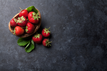 Fresh garden strawberry in bowl on stone table. Top view with copy space