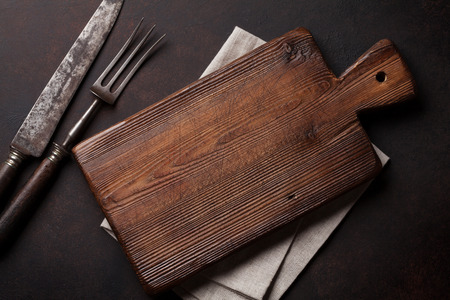 Old vintage kitchen utensils. Fork, knife, cutting board. Top view 스톡 콘텐츠