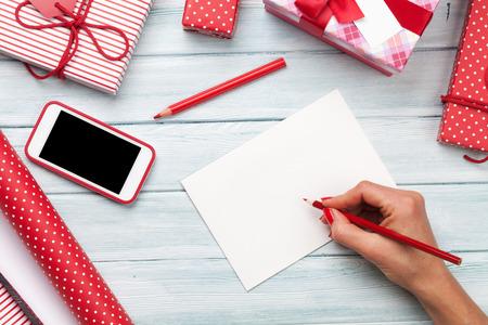 Grußkarte des weiblichen Schreibens und Verpackenweihnachtsgeschenke. Draufsicht mit Textfreiraum