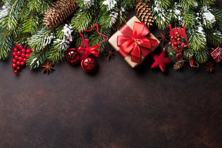 Christmas stone background with snow fir tree, gift box and decor. Top view with copy space