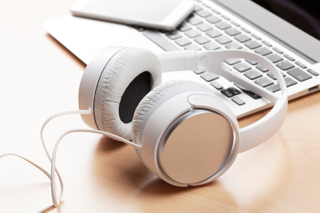 Headphones over laptop on wooden desk table.