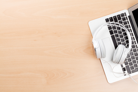 Headphones over laptop on wooden desk table. Music concept. Top view with copy space Stock Photo
