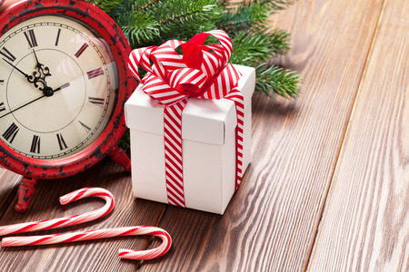 Christmas alarm clock, gift box and fir tree branch on wooden table