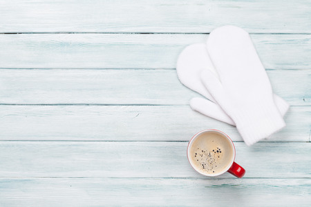 Christmas background with coffee and mittens on wooden table. Top view with copy space