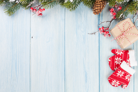 Christmas wooden background with snow fir tree and gift box. Top view with copy space Reklamní fotografie
