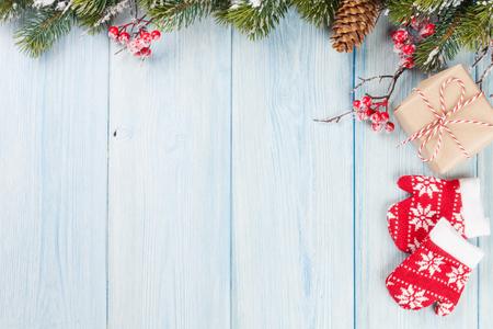 Weihnachtshölzerner Hintergrund mit Schneetannenbaum und Geschenkbox. Draufsicht mit Kopienraum Standard-Bild