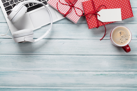 Christmas gift boxes, laptop, headphones and coffee cup on wooden background. Top view with copy space for text Stock Photo