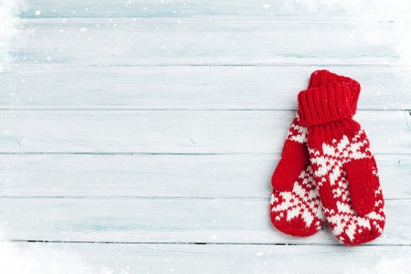 Christmas wooden background with mittens. Top view with copy space