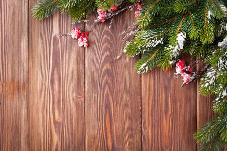 Fondo di legno di Natale con l'albero di abete della neve. Visualizza con copia spazio