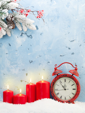 Christmas background with candles, alarm clock and snow fir tree in front of stone wall with copy space