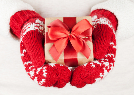 Female hands holding christmas gift in red mittens