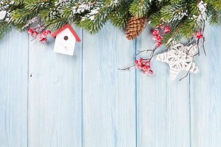 Weihnachtshölzerner Hintergrund mit Schneetannenbaum und -dekor. Ansicht mit Textfreiraum
