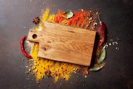 Various spices and cutting board on stone table. Top view with copy space