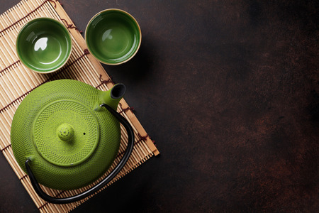 Green teapot and tea cups on stone table. Top view with copy space