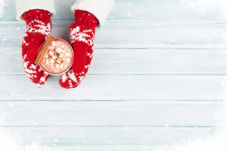 Female hands holding hot chocolate with marshmallow above wooden table. Top view with copy space