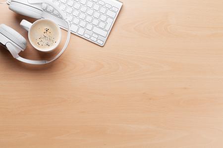 Kopfhörer über Tastatur und Kaffeetasse auf hölzerner Schreibtischtabelle des Büros. Musik-Konzept. Draufsicht mit Textfreiraum Standard-Bild