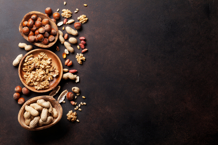 Various nuts on stone table. Top view with copy space