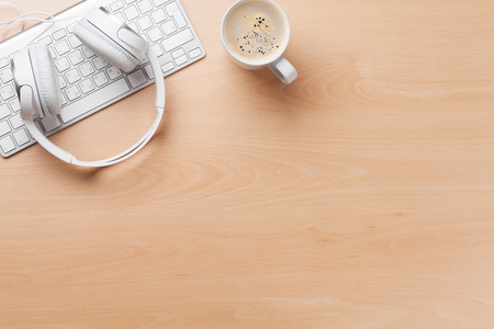 Hoofdtelefoons over toetsenbord en koffiekopje op kantoor houten bureau tafel. Muziek concept. Bovenaanzicht met kopie ruimte Stockfoto