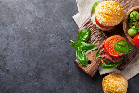 fried foods: Homemade burgers with beef, cheese, tomatoes, cucumber and basil on cutting board. Top view with copy space