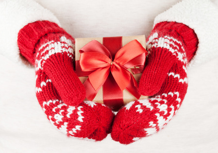 female christmas: Female hands holding christmas gift in red mittens